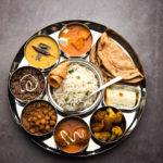 An Indian food platter of a variety of desi food dishes arranged in a circular fashion.