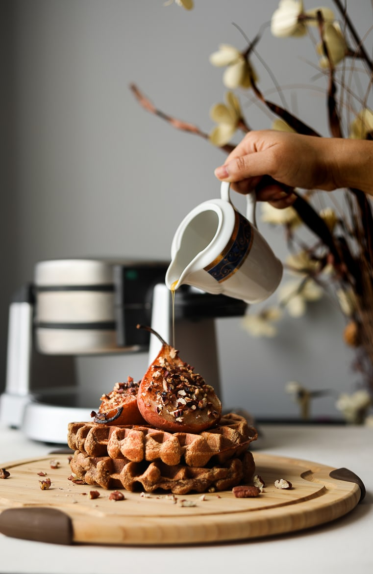 pouring maple syrup on a stack of brown waffles topped with baked pears and pecans with a waffle maker in the background