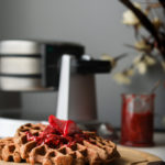 Strawberry chia jam topped on a brown waffle with a waffle maker in the background
