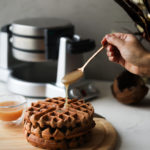 pouring caramel on a stack of brown waffles with a waffle maker in the background