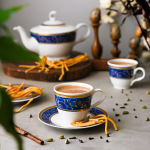 masala chai tea cup and saucer with a teapot in the background surrounded by plants and spices.