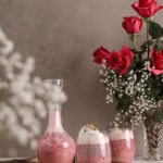 two glasses and a bottle of rose falooda in a tray with a backdrop of pink roses