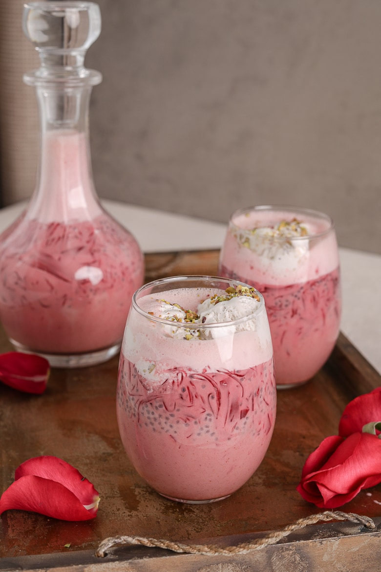 two glasses and a bottle of rose falooda in a tray with a tray