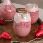 two glasses and a bottle of rose falooda in a tray with a pink rose on the side