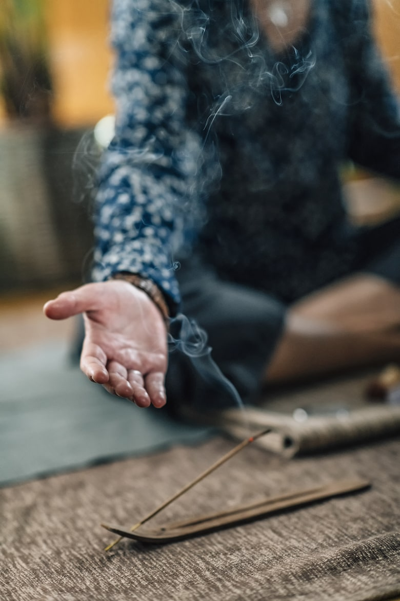 Burning incense stick with smoke and female hand with open palm during meditation at home.