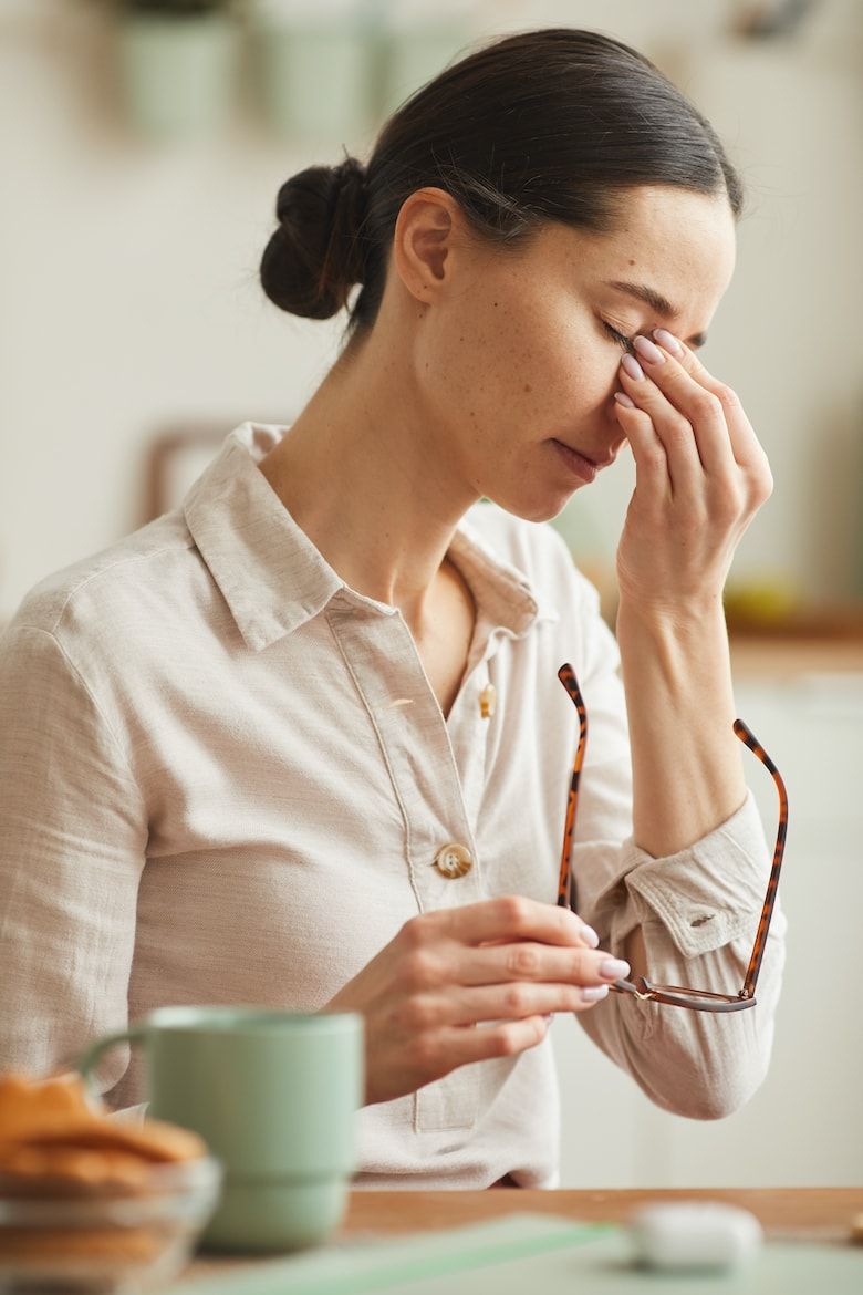 Vertical warm-toned portrait of tired young woman rubbing nose bridge and taking off glasses while suffering from headache
