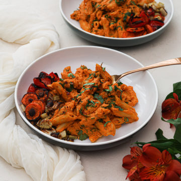 two bowls of creamy vegan pasta Indian style with a side of roasted vegetables and flowers in the foreground