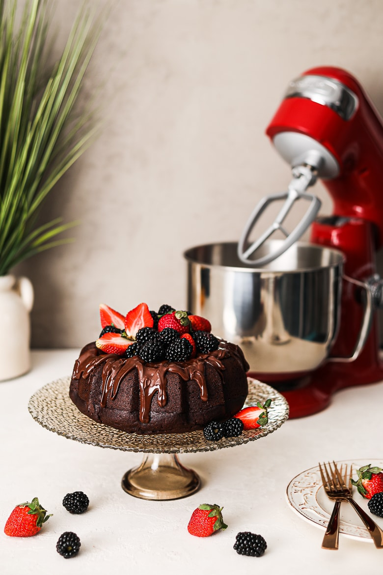 vegan chocolate cake bundt style on a stand topped with berries with a stand mixer in the background