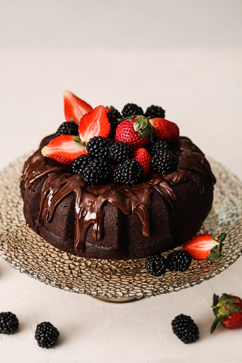 vegan chocolate cake bundt style on a stand topped with berries