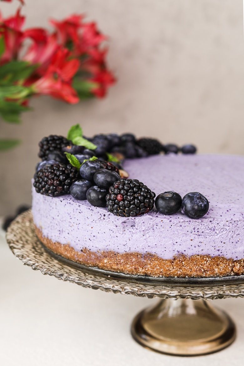 perspective shot of a blueberry dessert cake topped with black and blueberries, on a stand with flowers in the background - Ramadan 2021