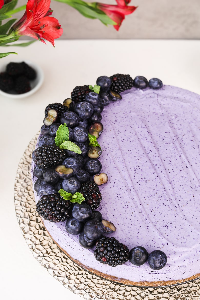 angle shot of a blueberry dessert cake topped with black and blueberries, on a stand.