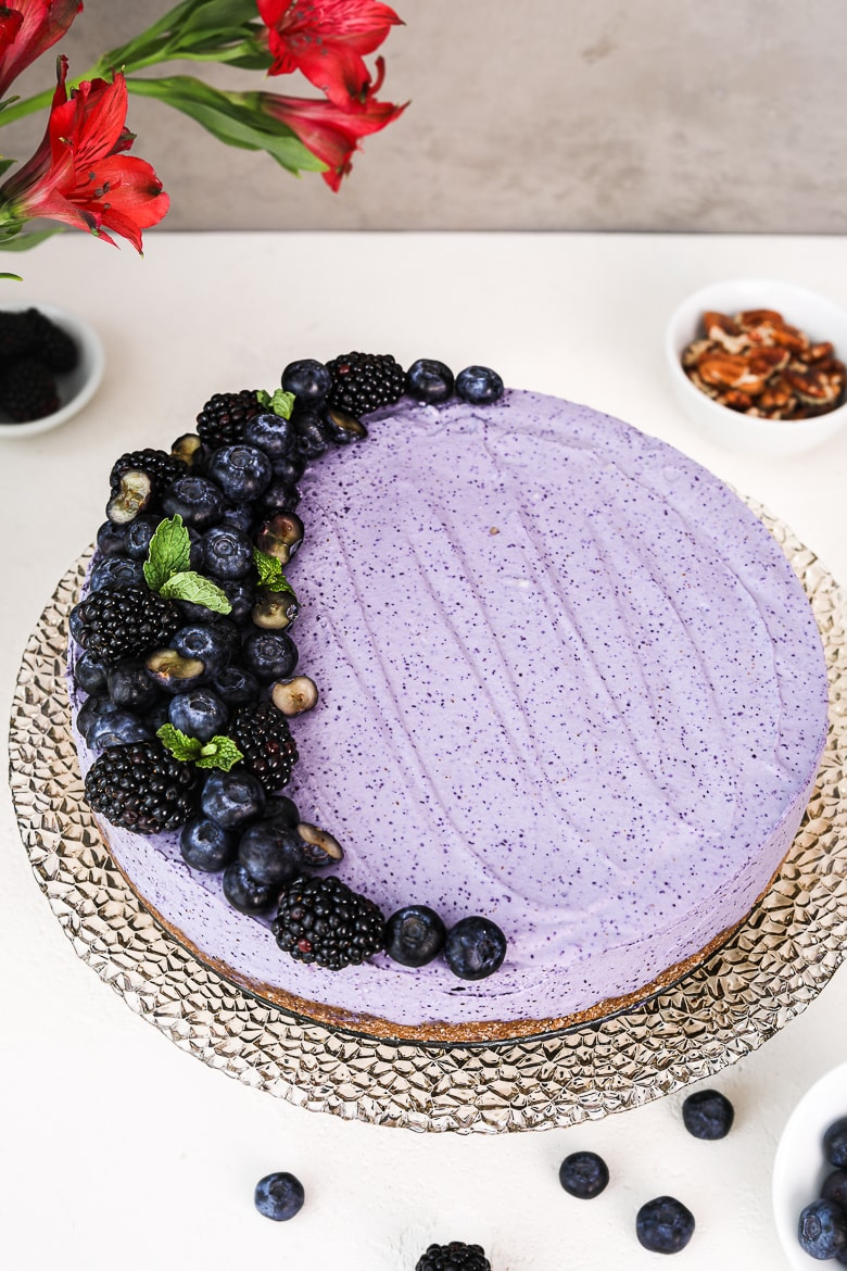 angle shot of a blueberry dessert cake topped with black and blueberries, on a stand with flowers and pecans in the background.
