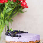 perspective shot of a blueberry dessert cake topped with black and blueberries, on a stand with flowers in the background.