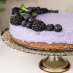 perspective shot of a blueberry dessert cake topped with black and blueberries, on a stand.