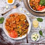 Bowl of vegetable quinoa with garlic shrimp recipe flat-lay
