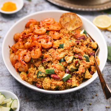Bowl of vegetable quinoa with garlic shrimp recipe flat-lay close up