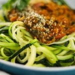 a bowl of zucchini noodles spaghetti topped with a simple curry sauce with lemon slices