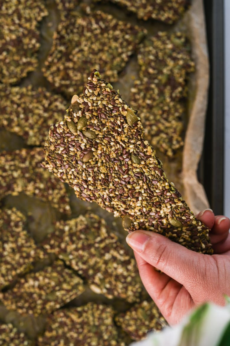 a hand holding a seeded cracker over a tray of backed seeded crackers of different shapes