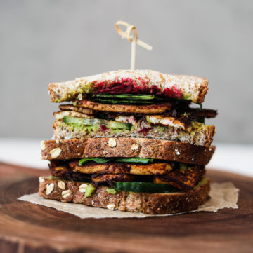 two half tofu sandwiches stacked on top of one another, filled with salad and beetroot on a wooden board
