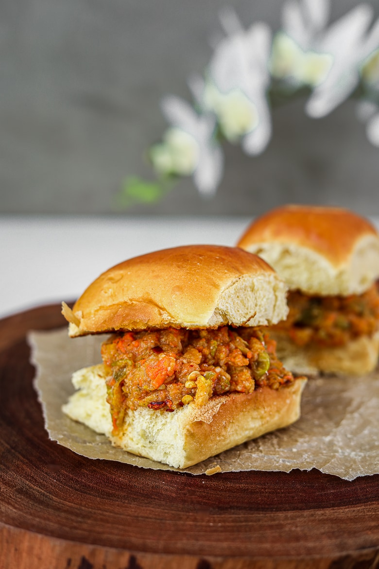 Indian pav bhaji filled in between two bread buns on a wooden board with white lily flowers in the background