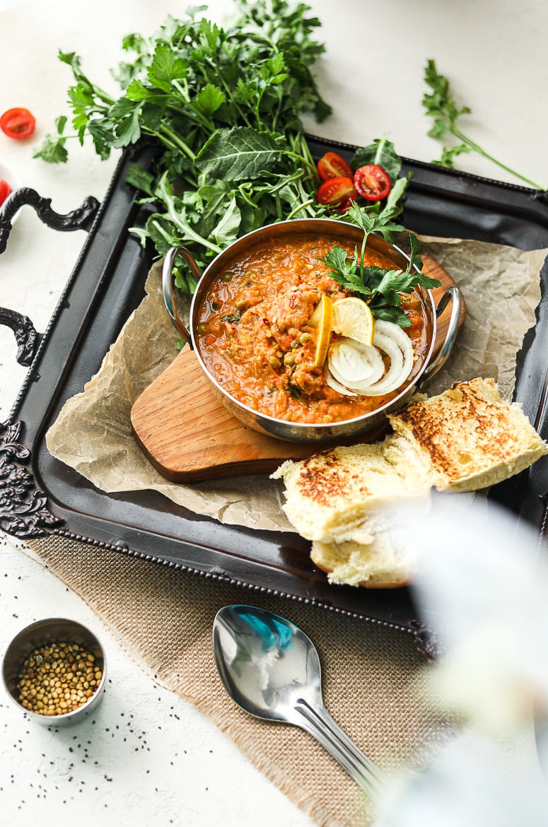 Bowl of Indian pav bhaji topped with onion slices and lemon segments on a black decorative tray with bread buns on the side and fresh herbs
