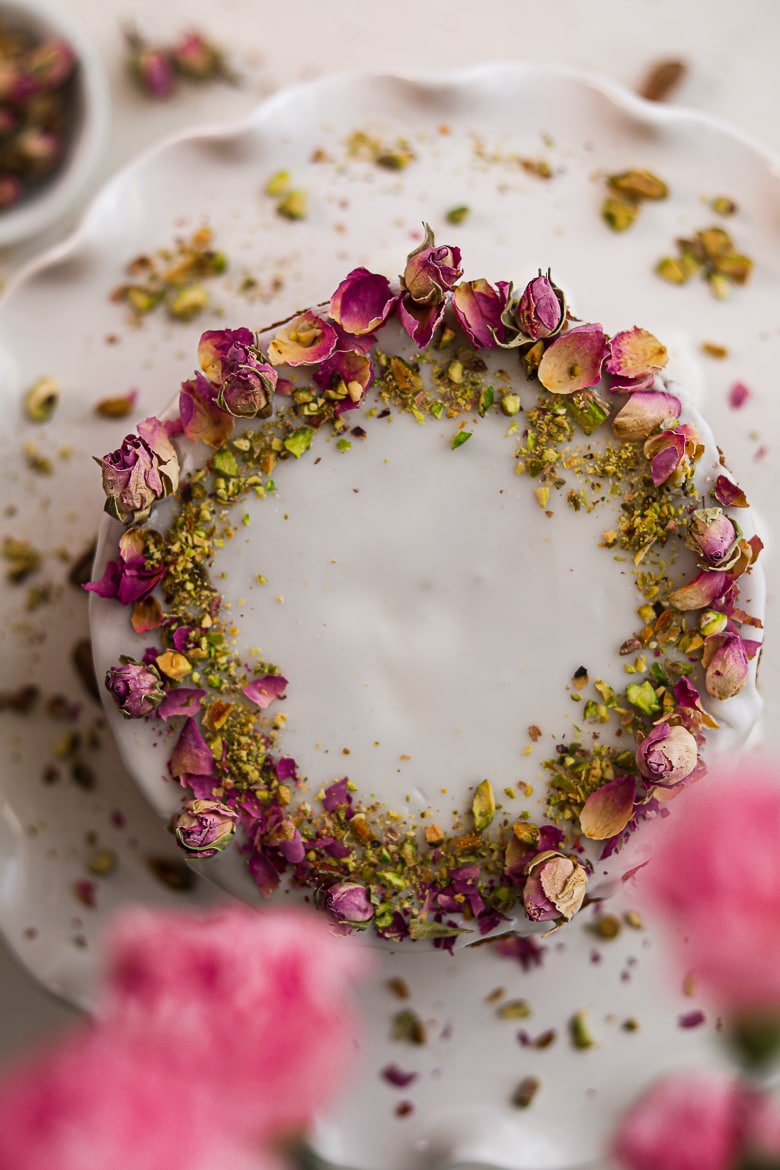 Persian love cake topped with icing and dried roses and crushed pistachios on a cake stand