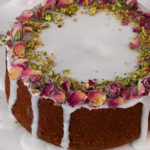 Persian love cake topped with icing and dried roses and crushed pistachios