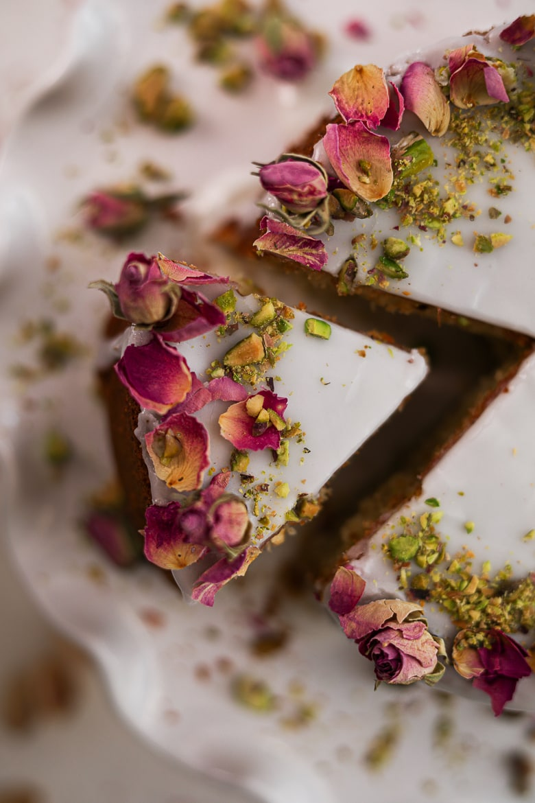 Persian love cake slice topped with icing and dried roses and crushed pistachios