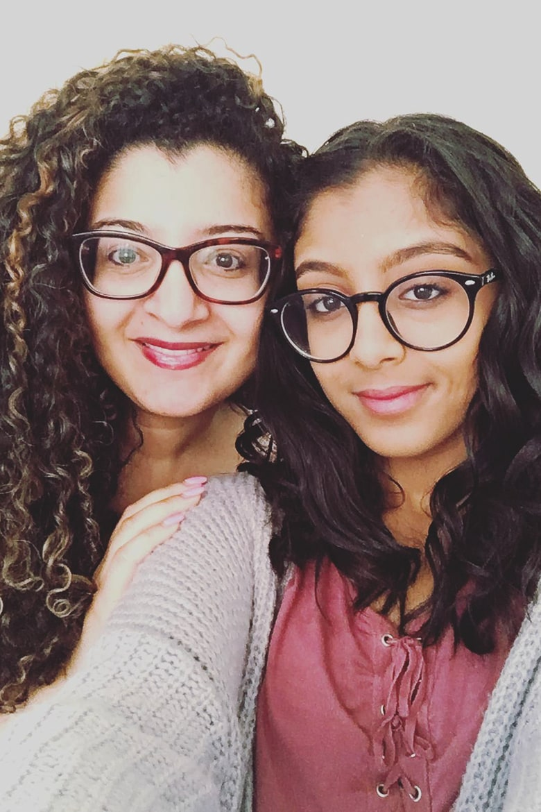 two ladies posing for the camera - one with straight hair and the other with curly hair