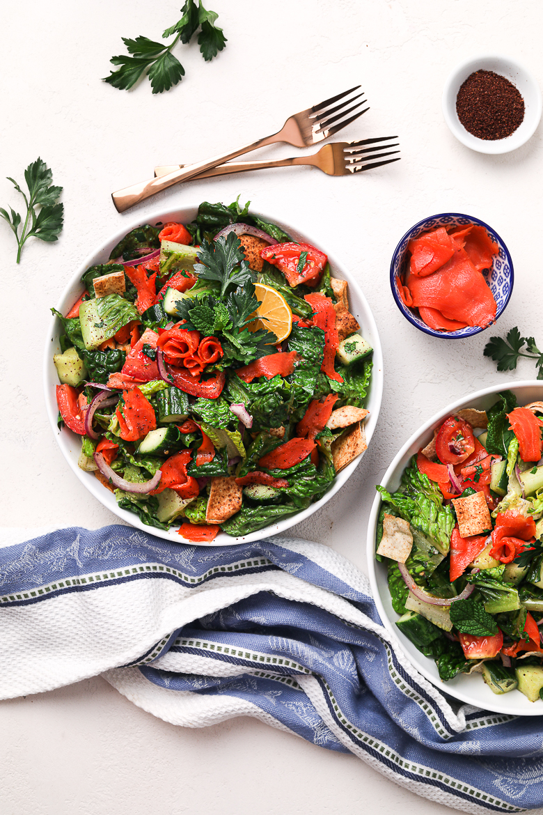 two bowls of fattoush salad flatlay with smoked salmon in a small bowl and sumac on the side with 2 gold forks