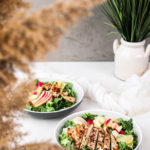two bowls of green leaf lettuce topped with spicy chicken salad and apple chunks - perspective shot