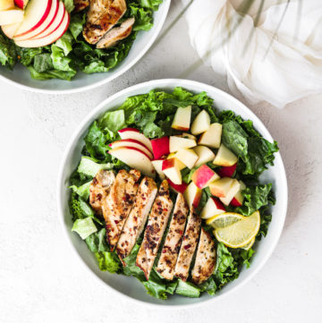 flatlay shot of a bowl of green leaf lettuce topped with spicy chicken pieces and apple chunks