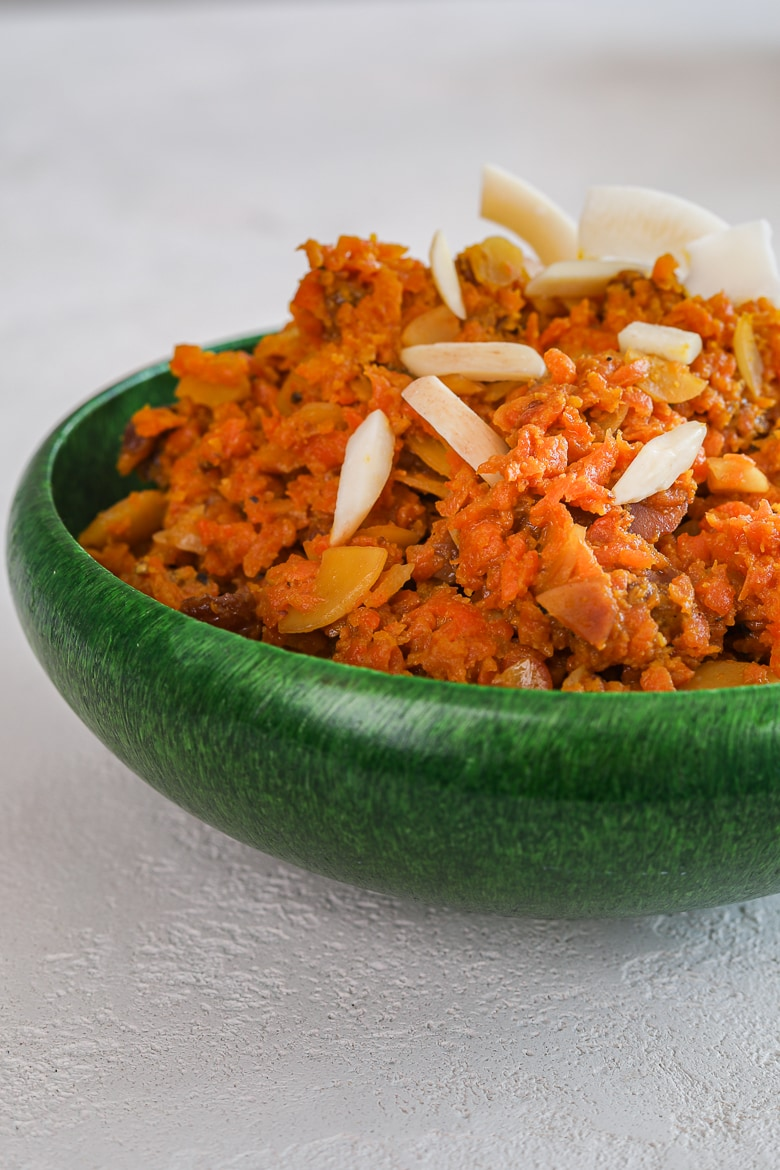 close up of green bowl with carrot halwa aka gajjar halwa - topped with nuts