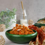 perspective shot of a green bowl with carrot halwa with a milk bottle in the background and wooden mesh balls in the foreground.