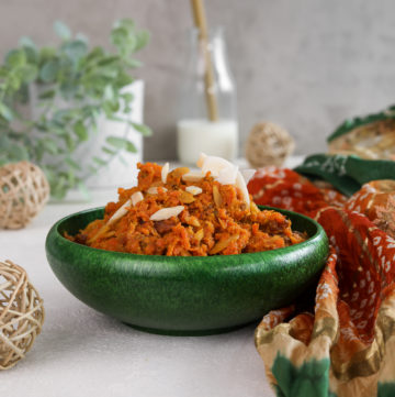 perspective shot of a green bowl with carrot halwa with a milk bottle in the background and wooden mesh balls in the foreground with a traditional Indian shawl