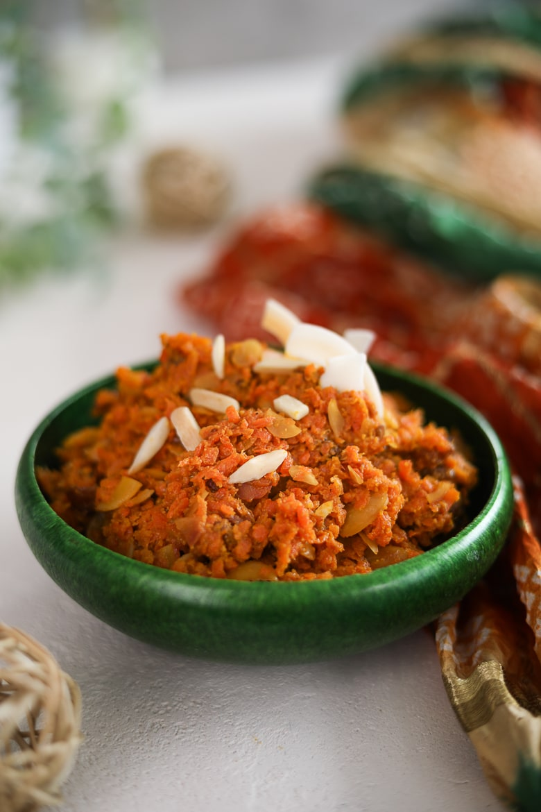a green bowl of carrot halwa topped with almonds and coconut shavings.