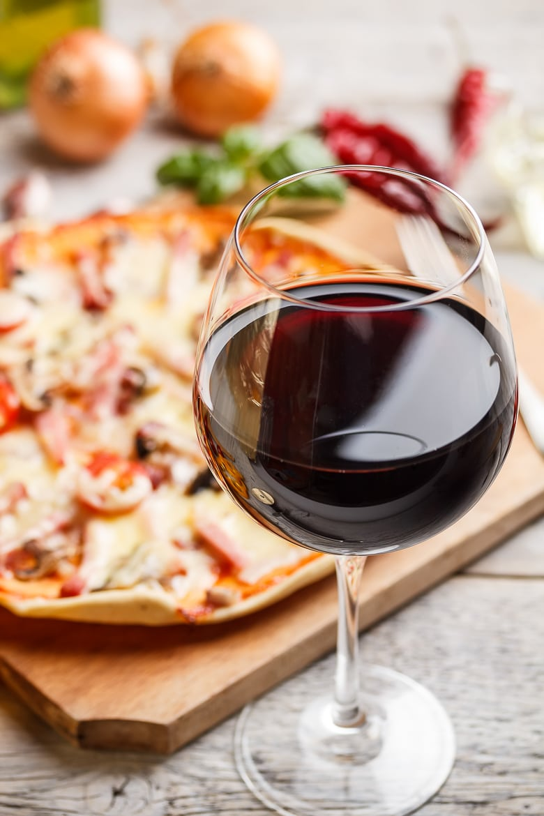 Glass of red wine, pizza on background