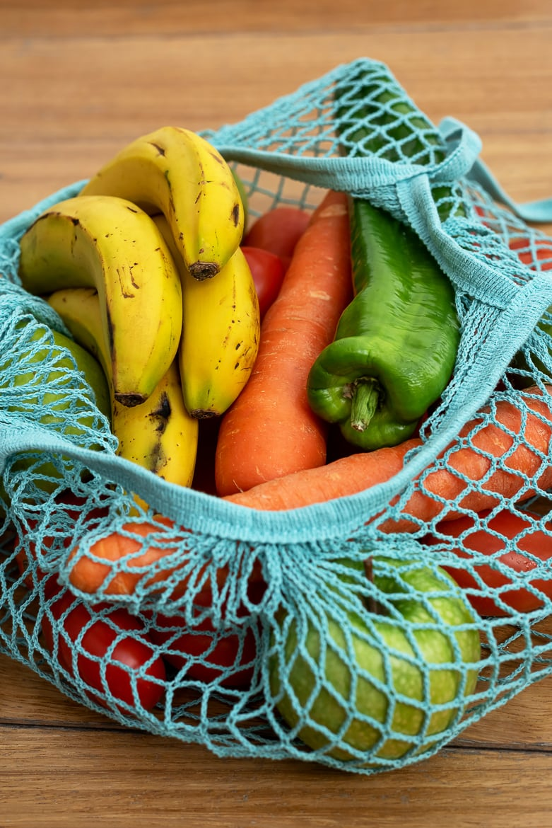 Cotton string eco bag with fruits and vegetables on wooden background