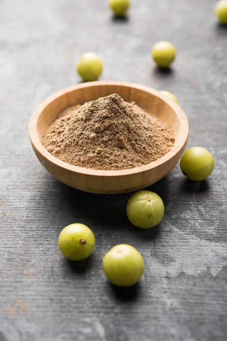 amla powder in a bowl with gooseberries all around