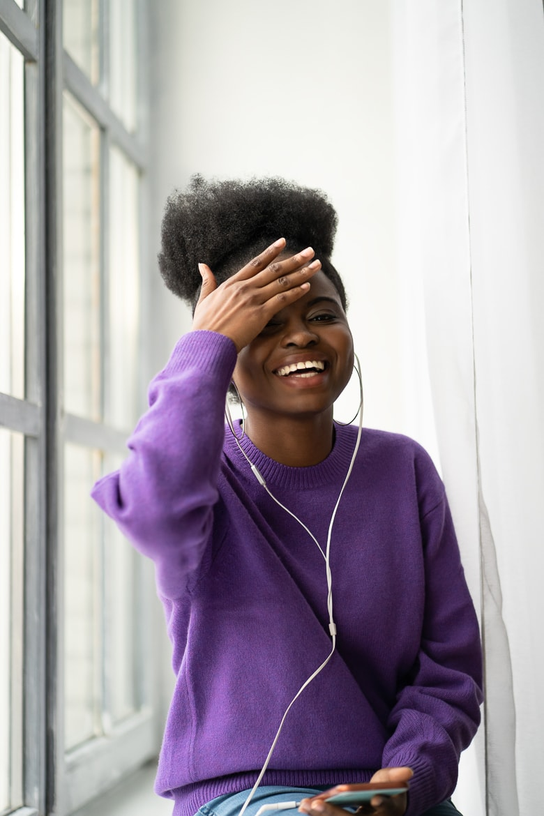 African American millennial young woman with afro hairstyle wear purple sweater laughing with toothy smile, sitting on windowsill, listens to music with headphones on smartphone, looking at camera.