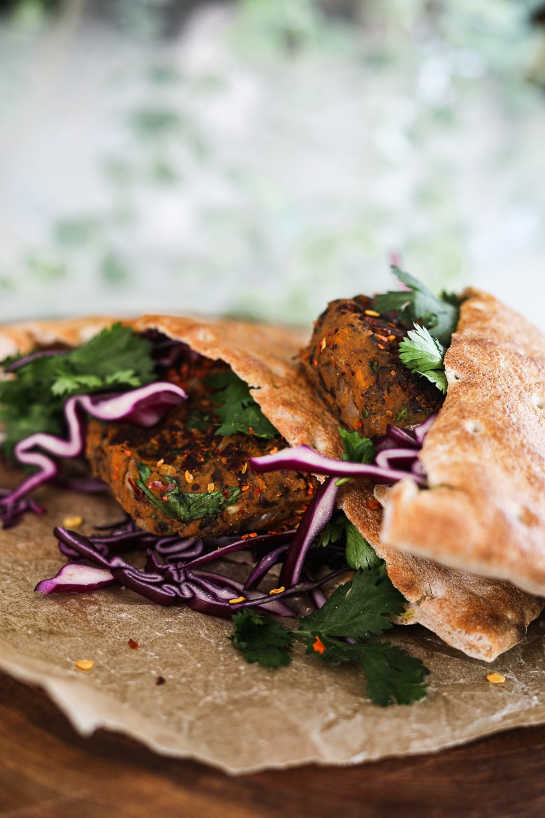 two pita breads stuffed with vegan kebab, purple cabbage and cilantro leaves