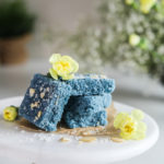 A stack of blue coconut barfi on a cake stand decorated with little yellow flowers