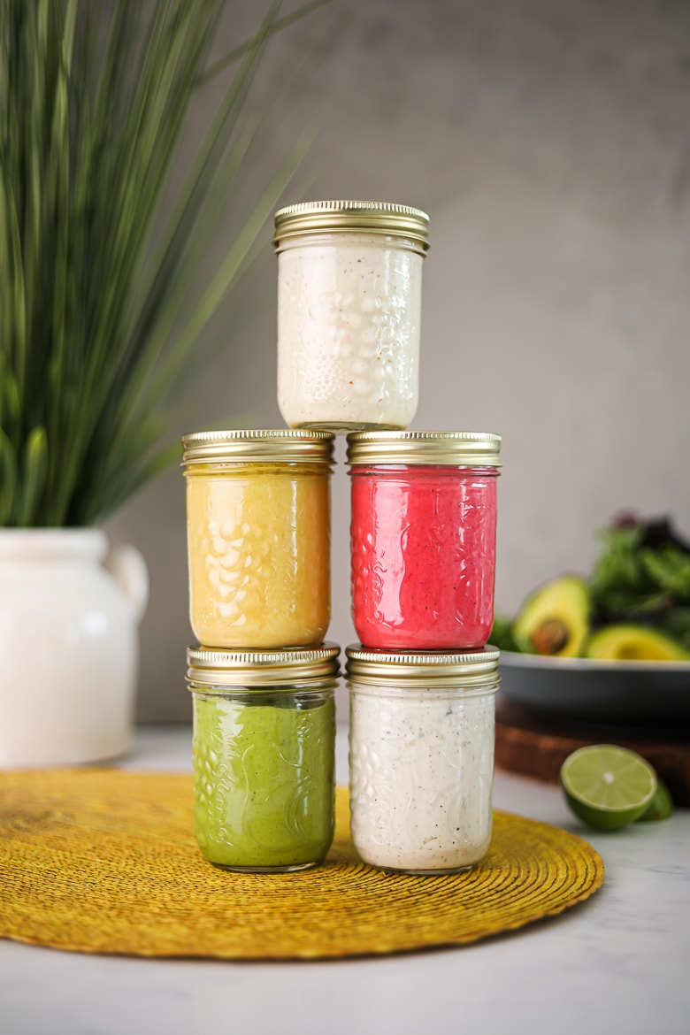 5 jars of colourful salad dressing recipes stacked on top of one another, on a yellow mat with a background of a bowl salad