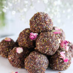 a pile of laddus - balls of Indian sweet dessert placed on a white marble cake stand sprinkled with dried roses