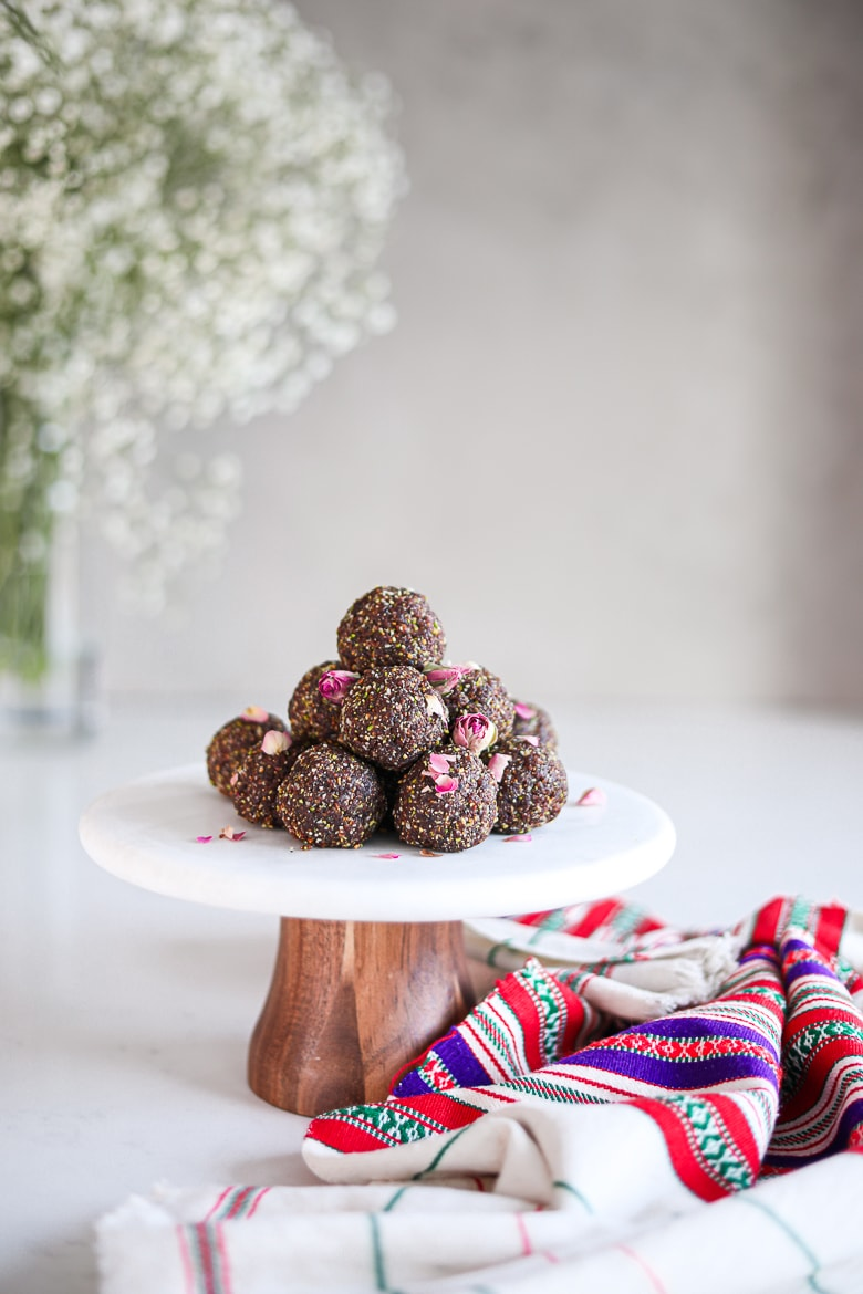 a pile of laddus - balls of Indian sweet dessert placed on a white marble cake stand sprinkled with dried roses with a traditional shawl on the countertop