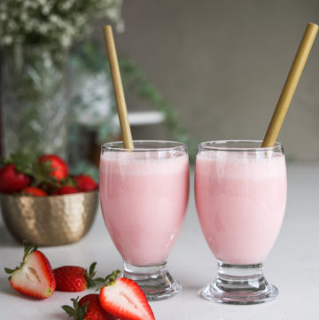 two glasses of strawberry lassi drink side by side with bamboo straw dipped inside alongside a bowl of fresh strawberries with white flowers in the background