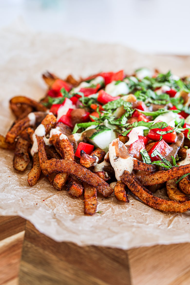 Spicy oven baked french fries loaded with peppers, cucumber and dressings with chopped herbs on a wooden board