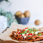 Spicy oven baked french fries loaded with peppers, cucumber and dressings with chopped herbs on a wooden board with raw potatoes and plants in the background
