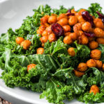 bowl of kale salad with spicy roasted chickpeas topped with cranberries