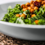 perspective shot of a grey bowl of kale salad with spicy chickpeas topped with dried cranberries